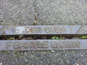 The worn mark of F. Bartle and Sons, Carn Brea on a pavement drain, Avondale Road, Truro.