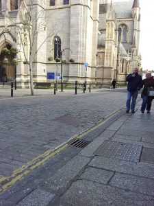 Manhole covers and gutter grill at High Cross, Truro Cathedral.